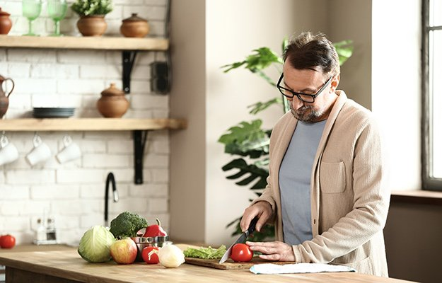 A middle-aged man cooking the healthy homemade meal | What Are Nootropics? 'Cognitive Enhancers' to Increase Mental Alertness