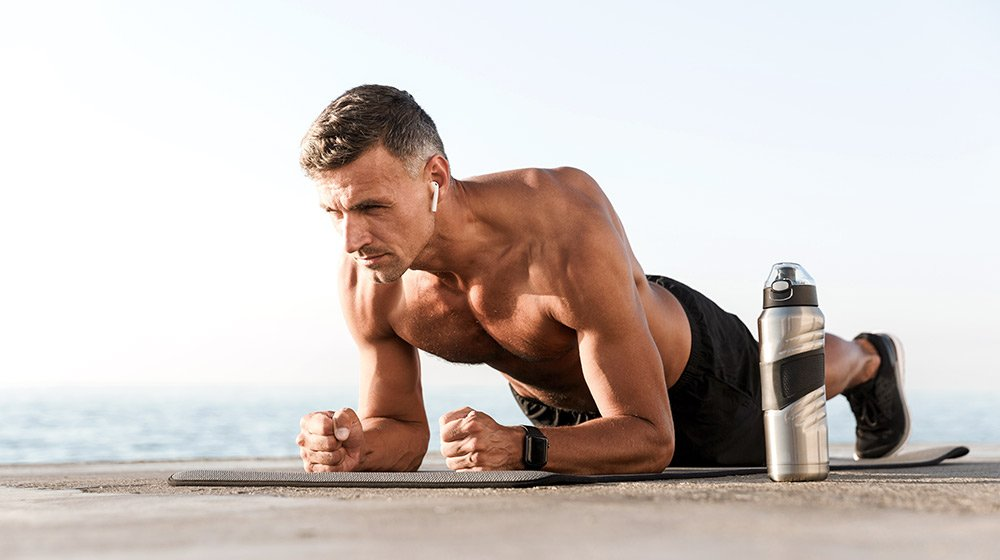 A middle aged man doing plank outdoor near the beach | Feature | 6 Ways To Battle Sarcopenia (Muscle Loss) And Become Physically Fit
