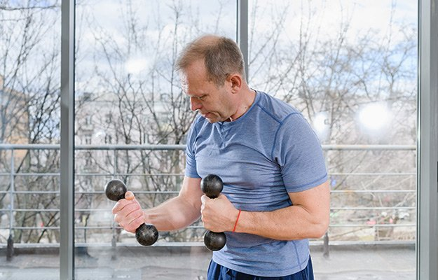 A middle aged man lifting light weight | What Causes Osteoporosis in Men and Who Is Vulnerable to This Bone Disease?