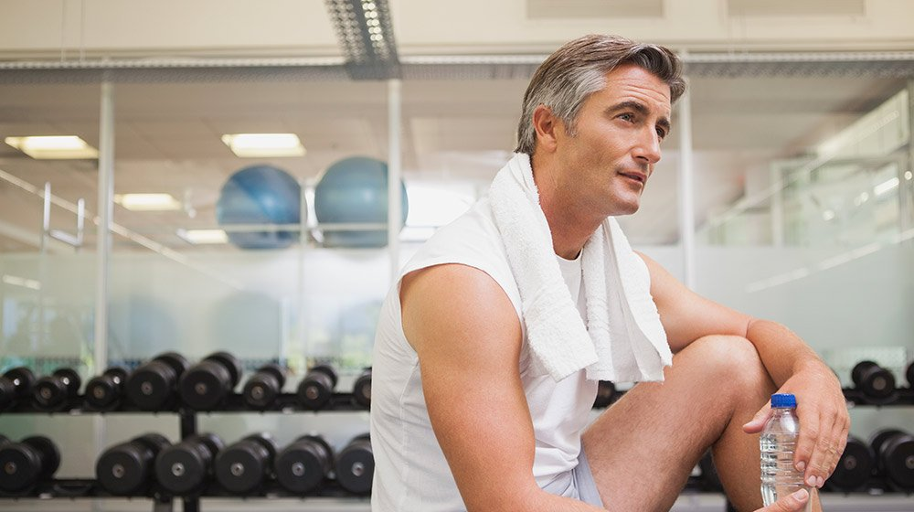 A middle aged man resting in a gym   Feature   How Does BHRT Help with Weight Loss?