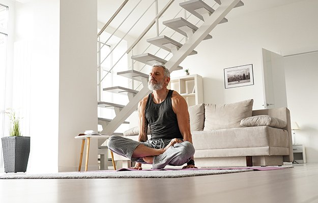 A strong middle aged man doing yoga at home   How A Strong Immune System Could Be The Best Response To COVID-19 & Its Variants